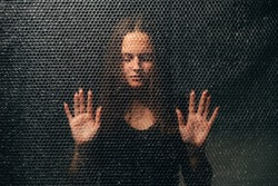 Peaceful woman. Soul healing. Spiritual practice. Esoteric mystery. Textured portrait of relaxed lady in black with closed eyes touching plastic bubble wrap wall in darkness.