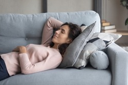 Peaceful young happy woman lying on soft pillow on comfortable sofa in living room, enjoying lazy weekend time. Calm pleasant millennial girl napping daydreaming alone on couch, resting indoors.