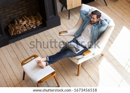 Peaceful young man resting with closed eyes in cozy armchair with laptop top view, successful serene male sitting with hands behind head, enjoying lazy leisure time, daydreaming during break at home
