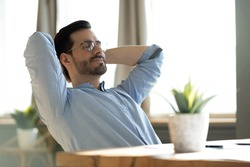 Peaceful young man wearing glasses daydreaming with closed eyes, lazy sleepy businessman or student leaning back in comfortable chair, stretching hands, sitting at work desk, dreaming and visualizing