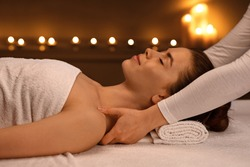 Peaceful young woman having relaxing full body massage at newest luxury spa decorated with candles. Female therapist rubbing sleeping lady shoulders, giving relaxing and body care session, side view