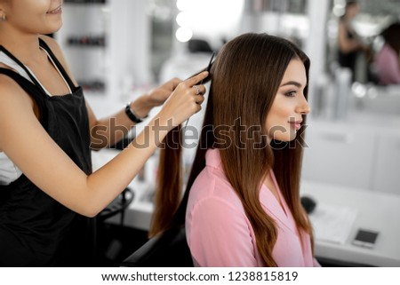 Peaceful young woman smiling and looking glad while sitting in the beauty salon and getting new haircut
