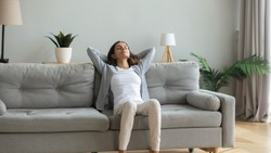 Peaceful young woman with hands behind head relaxing on cozy sofa at home, daydreaming and meditating, satisfied serene girl leaning back, stretching on comfortable couch in living room