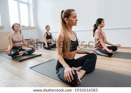 Peaceful young women practicing yoga in a group of four, sitting on a floor with legs closely tucked. Meditation, relaxing, clearing consciousness. Eyes closed, hands on knees.