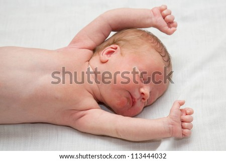 Peacefully and soundly sleeping naked newborn tiny slim baby, few days old. His hands clenched into fists. He sleeps on the white sheet.
