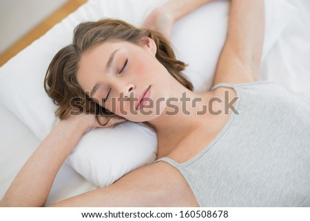 Peacefully sleeping woman lying on her white bed in the bedroom