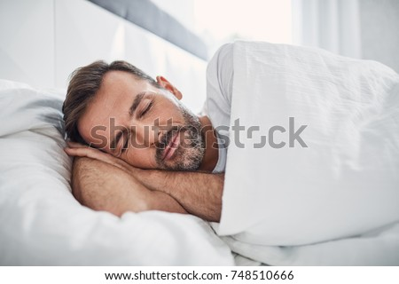 Peacefulness concept. Handsome man sleeping in bed
