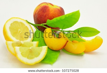 Peach and peach slices, lemon slices and lemon with green leaves