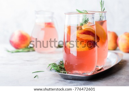 Peach and rosemary lemonade, cocktail on a gray stone concrete table background. Summer drink