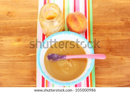 Peach baby food in a plate on colorful napkin on wooden table close-up