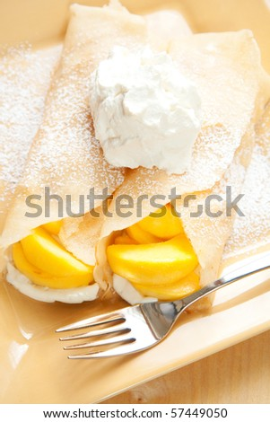 Peach crepes with a large dollop of whipped cream