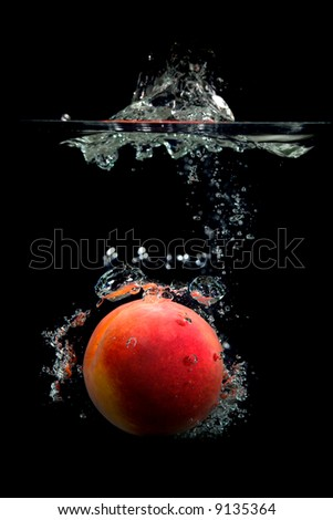 Peach dropped into water with bubbles