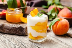 Peach fruit dessert in glass cup on rustic wooden table with fresh peach fruit, peach jam. Homemade dessert with fruits. Fruit salad with yogurt or sour cream.