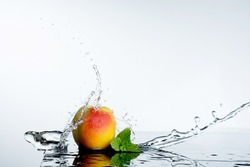 Peach in spray of water. Juicy peach with splash on white background.