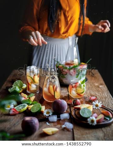 Peach lemonade with strawberries, limes, summer lemonade with ice on the black dark rustic background. Women pours lemonade to the glass, splash of lemonade