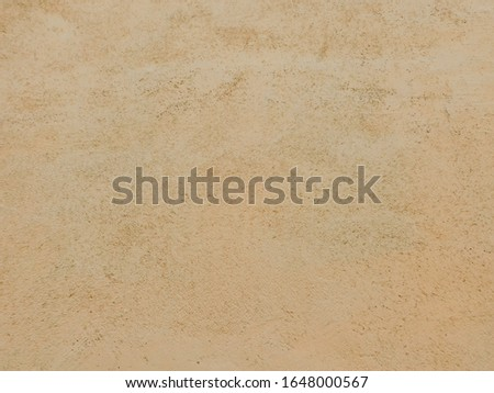 Peach painted concrete wall with a rough structure.  Background with a rough texture