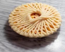 peach pie with spiral lattice on white marble