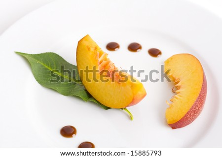 peach slices and leaf on white plate