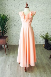 Peach vintage fashion long maxi dress chiffon ruffle neck bridesmaid wedding luxury dress tailor made by a dressmaker, a dress on mannequin sewing dress form in the plain room