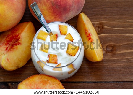 peach yogurt, sweet summer dessert. Curd dessert with fresh fruits. Eating healthy, vitamin-rich Breakfast. yogurt with slices of fresh peaches and whole peaches on a wooden background. close up.