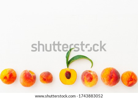 Peaches and peach in halves with leaves on white wooden background. Flat lay composition with ripe juicy peaches copy space. Harvest of peaches for food or juice. Top view fresh organic peach fruit.