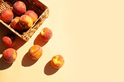 Peaches in a wicker basket on a gentle peach background. Contrast shadows