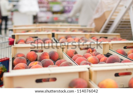 Peaches in wood boxes in supermarket
