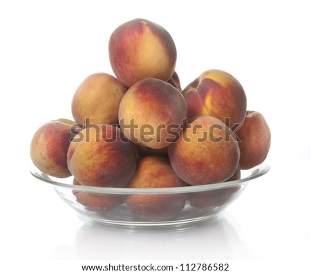 Peaches on glass bowl isolated on white background