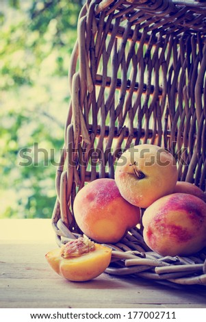 Peaches spilling out of a basket/ Ripe sweet peaches on wooden table
