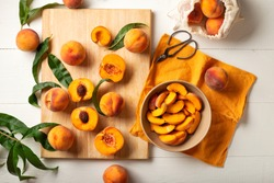 Peaches whole fruits with leaves, peaches in halves, peach slices on a white kitchen table. The process of making peach jam, cooking peach dessert on a cutting board. Pastry chef work place. Flat lay