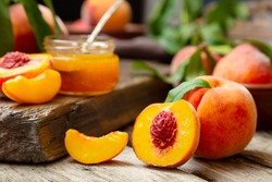 Peaches with leaves on dark wooden board with peach in halves with peach seed stone. Composition with ripe juicy peaches Harvest for food. Fresh organic fruit