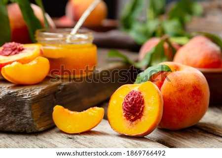 Peaches with leaves on dark wooden board with peach in halves with peach seed stone. Composition with ripe juicy peaches Harvest for food. Fresh organic fruit Photo stock ©