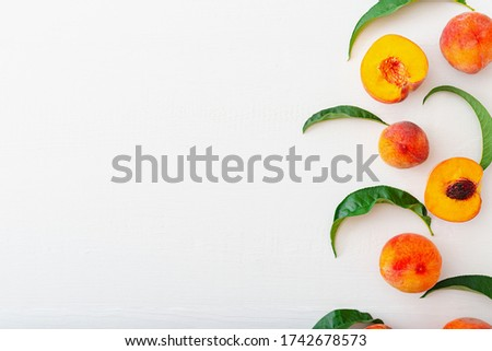 Peaches with leaves on white wooden background with peach in halves. Flat lay copy space composition with ripe juicy peaches. Harvest of peaches for food or juice. Top view fresh organic peach fruit.