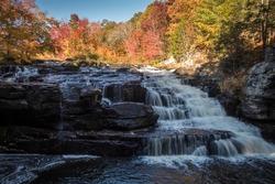 Peak fall foliage surrounds beautiful cascading downstream Shohola Falls on an Autumn morning in the Pennsylvania Poconos