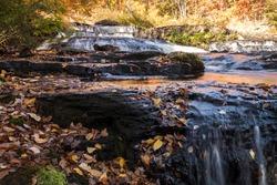 Peak fall foliage surrounds beautiful cascading middle Shohola Falls on an Autumn morning in the Pennsylvania Poconos