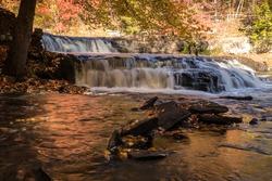 Peak fall foliage surrounds beautiful cascading upper Shohola Falls on an Autumn morning in the Pennsylvania Poconos