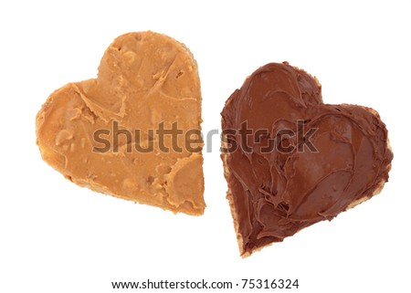 Peanut butter and chocolate spread on brown heart shaped wholemeal bread, over white background.