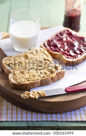 peanut butter and jelly sandwich with glass of milk, close up.
