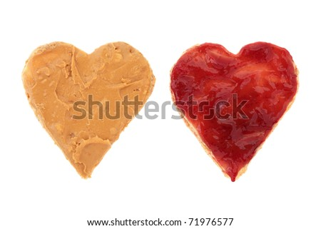 Peanut butter and raspberry jam on brown heart shaped wholemeal bread, over white background.