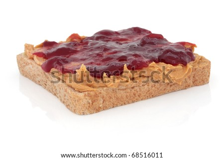 Peanut butter and raspberry jam on brown wholemeal bread, over white background.