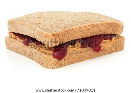Peanut butter and raspberry jam sandwich on brown bread, over white background.