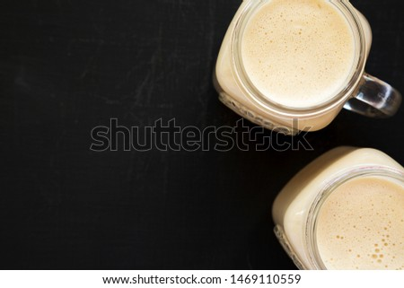 Peanut butter banana smoothie in glass jars on a black background, overhead view. Overhead, flat lay, from above. Copy space. #1469110559