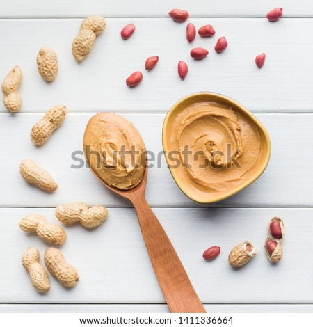 Peanut butter in bowl and spoon and scattered peanuts on white wooden background, top view. Artisan peanut butter concept #1411336664
