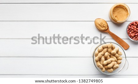 Peanut butter in jar and spoon and bowls of peanuts on white wooden background, top view, copy space #1382749805