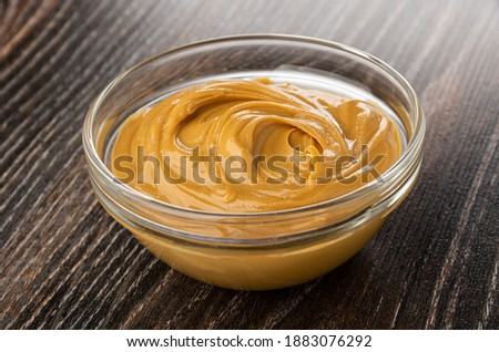Peanut butter in transparent glass bowl on dark wooden table Foto stock ©