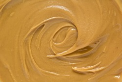 Peanut butter texture background. Natural nut paste swirl close up. Brown color creamy spread top view