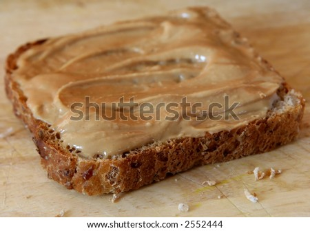 Peanut butter toast on wooden choping board, macro close up with copy space