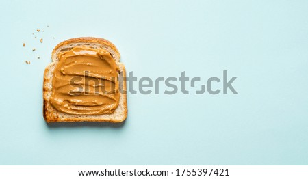 Peanut butter toast (sandwich) on blue (menthol) background. Banner. Copy space. Fresh and healthy traditional american breakfast, dessert or snack made of toasted bread and peanut butter.