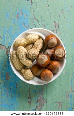 Peanuts and hazelnuts on the vintage wooden surface.