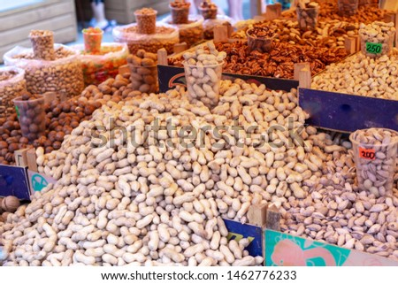 peanuts are piled on the counter in a large pile, alongside other types of nuts, on the market for sale